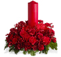 holiday floral arrangement with red candle. Filled with Christmas greens, red carnations, red roses  and ribbon