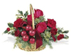 holiday basket arrangement is filled with Christmas greens, red carnations, red roses, red berries and ribbon.